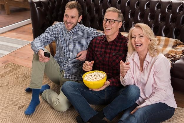 Tv kijken en popcorn eten en gelukkige familie Gratis Foto