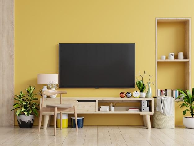 Tv Op Kast In Moderne Woonkamer Met Lamp Tafel Bloem En Plant Op Gele Muur Premium Foto