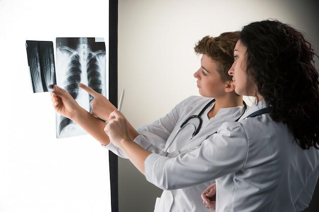 Twee aantrekkelijke jonge artsen die x-ray resultaten bekijken Gratis Foto