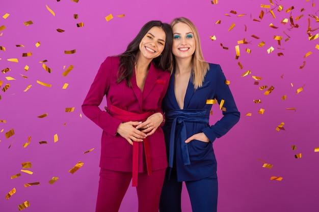 Twee aantrekkelijke vrouwen vieren nieuwjaar op violette muur in stijlvolle kleurrijke avondpakken van paarse en blauwe kleur, vrienden samen plezier hebben, modetrend, gouden confetti feeststemming Gratis Foto