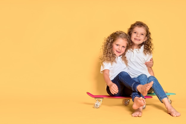 Twee actieve en gelukkige meisjes met krullend haar met plezier met cent board, Premium Foto