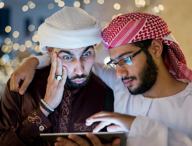 Twee arabische mannen met tablet in de stad 's nachts Premium Foto