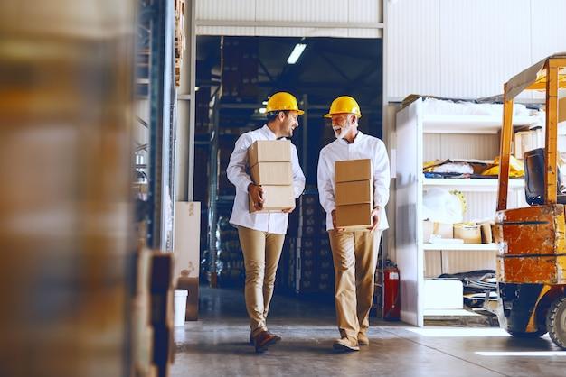Twee arbeiders in witte uniformen en met gele helmen op hun hoofd verplaatsen zware dozen in het magazijn. Premium Foto