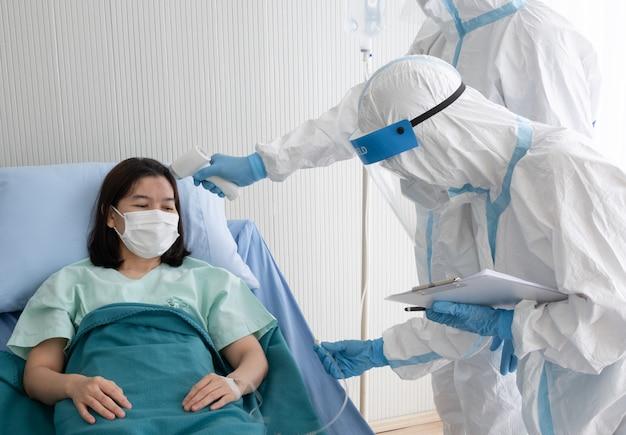 Twee artsen dragen een pbm-pak met gezichtsmasker, meten de lichaamstemperatuur van een met coronavirus geïnfecteerde patiënt met een infraroodthermometer in een quarantainekamer met negatieve druk. Premium Foto