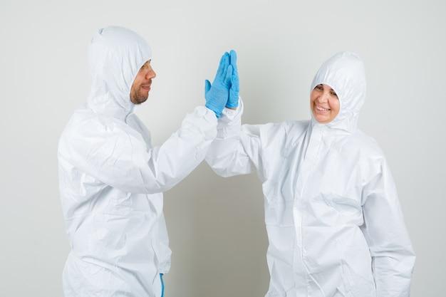 Twee artsen in beschermend pak, handschoenen die in handen klappen en gelukkig kijken Gratis Foto