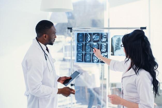 Twee artsen kijken naar een röntgenfoto en bespreken het probleem. medische technici die op mri-röntgenstraal van patiënt richten. radioloog die röntgenstraal controleert. medisch en radiologieconcept. Premium Foto