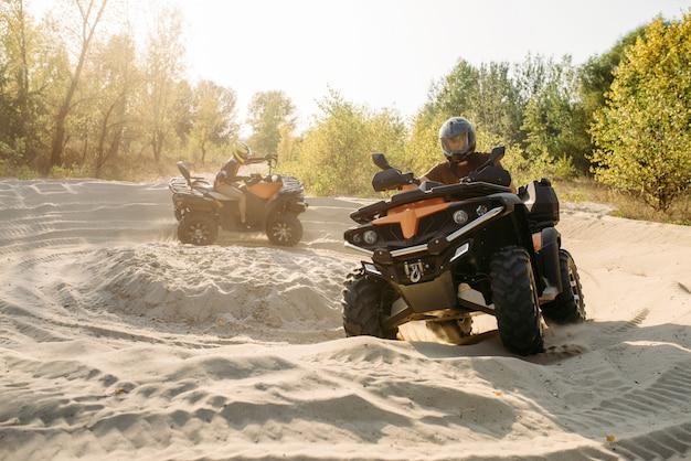 Twee atv-rijders in helmen rijden in een cirkel op zand Premium Foto