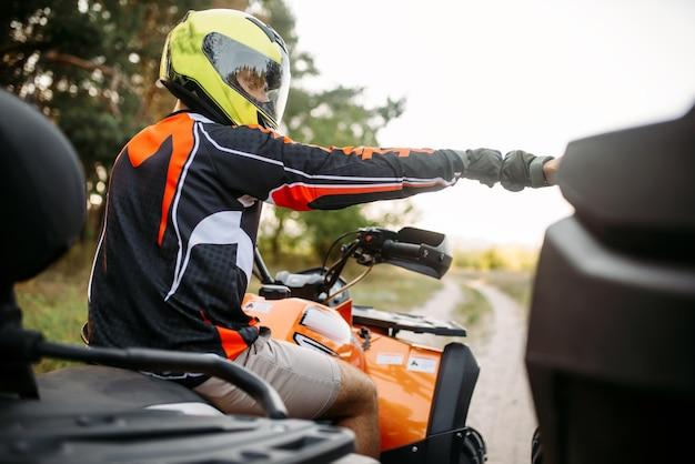 Twee atv-rijders slaan vuisten voor geluk, achteraanzicht Premium Foto