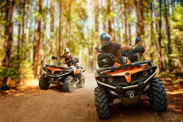 Twee atv-ruiters in helmen, snelheidsrace in bos, vooraanzicht. rijden op een quad, extreme sporten en reizen, quadbike offroad-avontuur Premium Foto