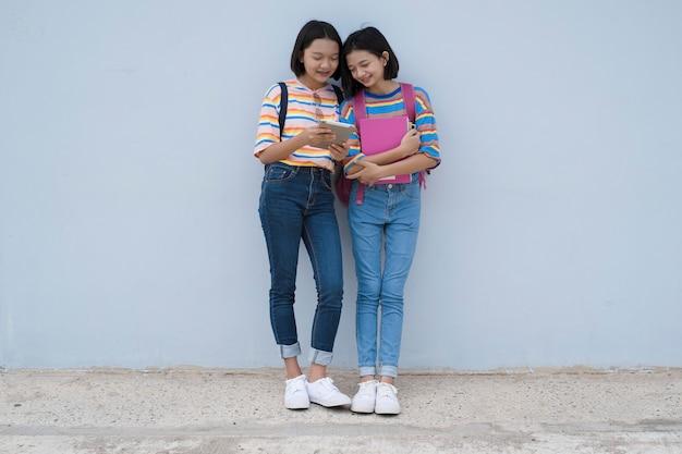 Twee aziatisch studenten jong meisje die laptop op school op blauwe muur kijken Premium Foto