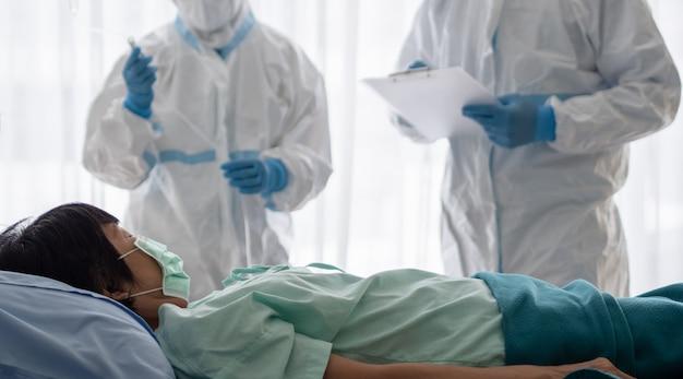 Twee aziatische artsen dragen een pbm-pak met een n95-masker en een gelaatsscherm, behandelen en gebruiken een zuurstofmasker met een coronavirus-geïnfecteerde patiënt in een kamer met negatieve druk. Premium Foto