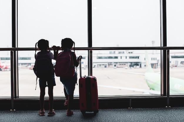 Twee aziatische kind meisjes met rugzak vliegtuig kijken en wachten op instappen in de luchthaven Premium Foto
