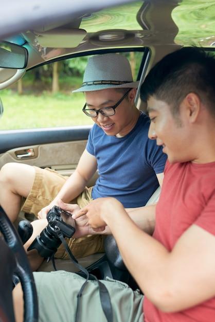 Twee aziatische mannelijke vrienden die in auto zitten en foto's controleren op digitale camera Gratis Foto
