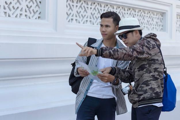 Twee aziatische mannenreizigers die kaart zoeken bij een tempel rachaburana, wat zijn de attractieslocatie op de kaart. Premium Foto