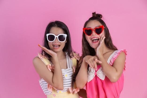Twee aziatische meisjes die vrienden zijn, zijn gelukkig en hebben een roze. Gratis Foto
