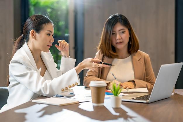 Twee aziatische onderneemsters die met de partnerzaken door puntpen aan technologielaptop werken Premium Foto