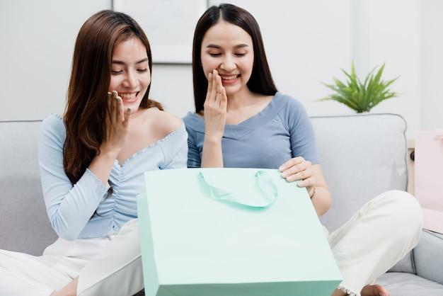 Twee aziatische schoonheidsmensen die de papieren zak openen met een blij lachend gezicht. nieuw normaal online zakendoen in de winkelervaring vanuit huis Premium Foto