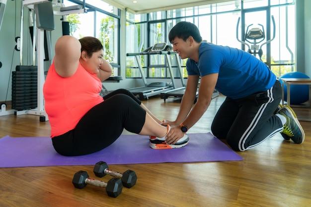 Twee aziatische trainer man en overgewicht vrouw zitten samen te oefenen in de moderne sportschool Premium Foto