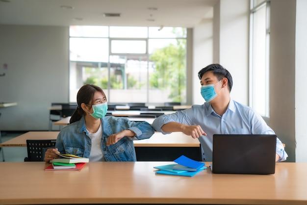 Twee aziatische universiteitsstudenten die met gezichtsmasker ontmoeten en vriend begroeten door de elleboog aan te raken Premium Foto