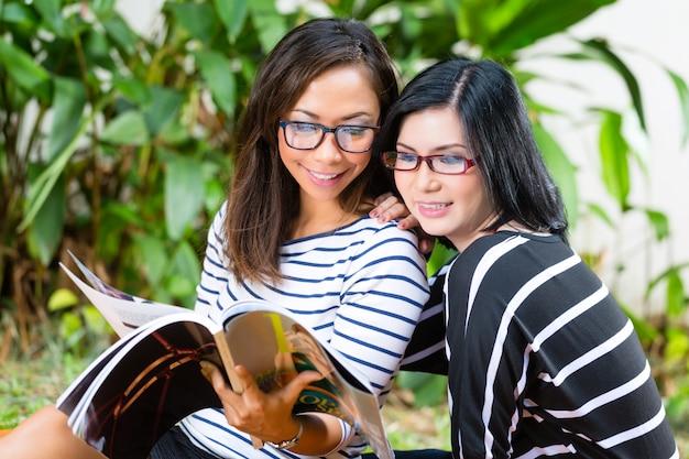 Twee aziatische vriendinnen lezen magazine Premium Foto