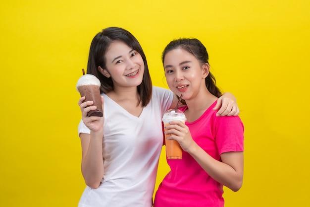 Twee aziatische vrouwen die bevroren melkthee en bevroren cacao op een geel drinken. Gratis Foto