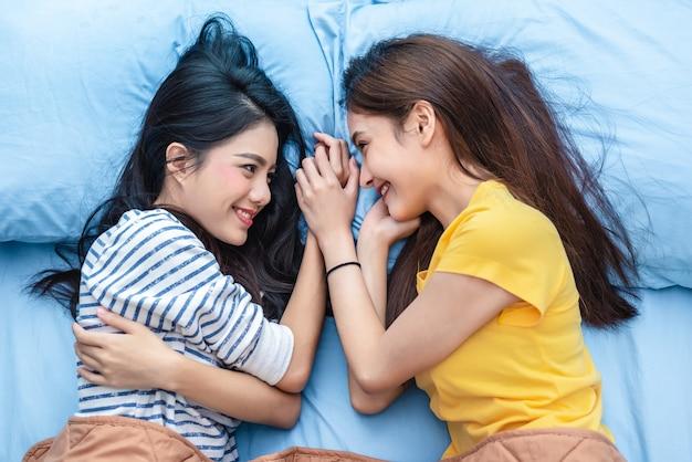 Twee aziatische vrouwen die elkaar bekijken wanneer het liggen op bed Premium Foto