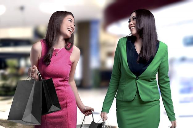 Twee aziatische vrouwen die het winkelen zakken in de wandelgalerij dragen Premium Foto
