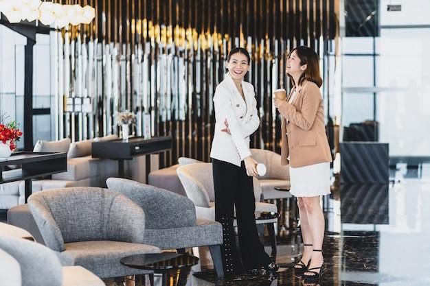 Twee aziatische zakenvrouwen praten tijdens koffiepauze in moderne kantoor of naaiatelier ruimte Premium Foto