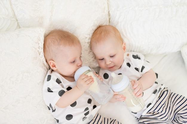Twee baby tweeling broer en zus van 8 maanden oud liggen op het bed in hun pyjama en drinken melk uit een fles, babyvoeding concept, bovenaanzicht, concept van vriendschap, plaats voor tekst Premium Foto