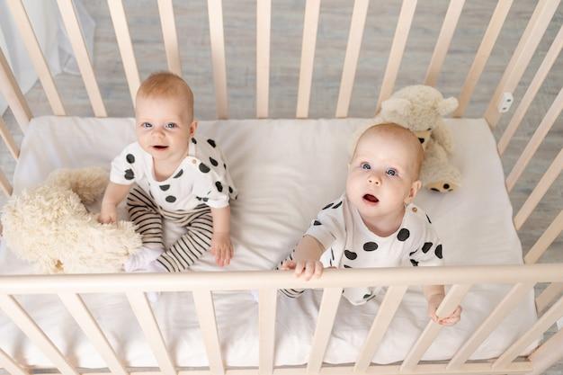 Twee baby tweelingen broer en zus 8 maanden zitten in hun pyjama in de wieg en kijken naar de camera Premium Foto