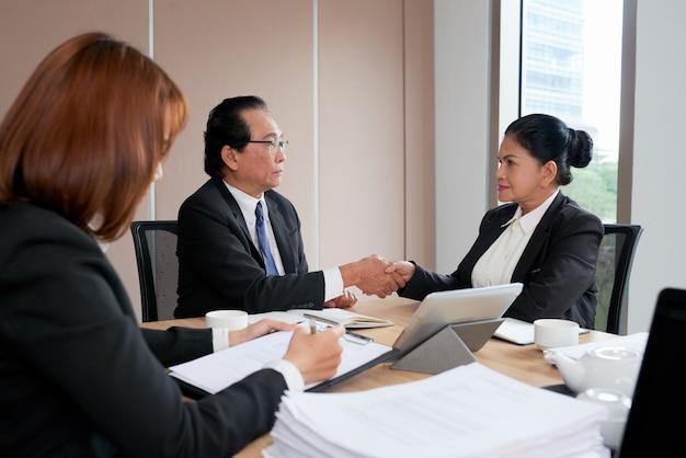 Twee bedrijfsleiders handenschudden om de deal te sluiten terwijl de secretaris de notulen van de vergadering protocolleert Gratis Foto