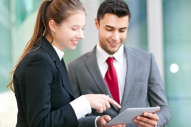 Twee bedrijfsmensen die een tablet in het stedelijke plaatsen gebruiken Premium Foto