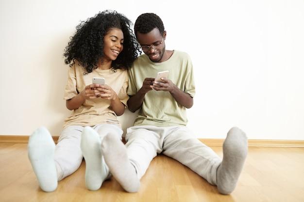 Twee beste vrienden die vrijetijdskleding dragen die plezier hebben binnenshuis, zittend op de vloer Gratis Foto