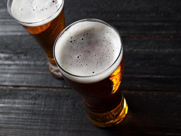 Twee bieren op een donkere houten tafel Premium Foto