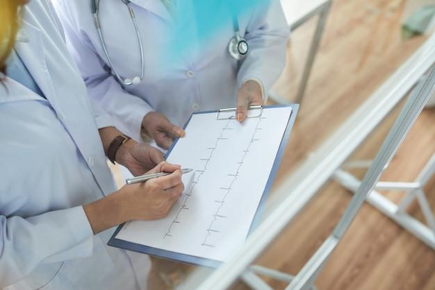 Twee bijgesneden cardiologen die cardiogrammen herzien in het medische kantoor Gratis Foto