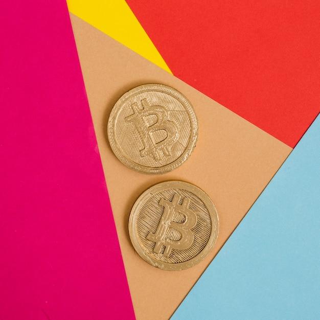Twee bitcoins op veel kleurrijke achtergrond Gratis Foto