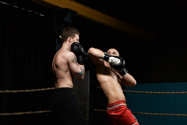 Twee boksers die vechten in boksring: man met getatoeëerde schouders staande in verdedigingspositie terwijl zijn tegenstander in rode broek elleboog op zijn gezicht richt. rivaliteit, confrontatie en competitie Gratis Foto