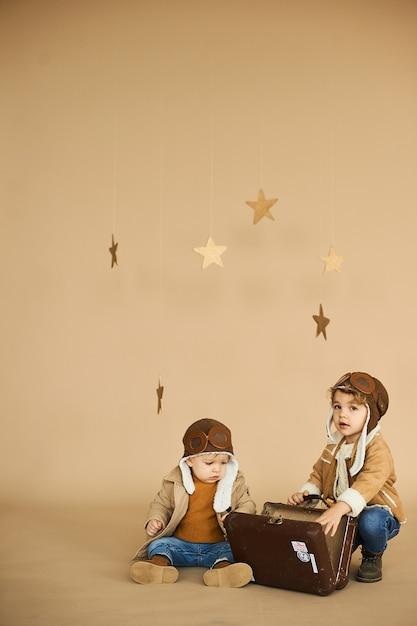 Twee broers worden gespeeld met een speelgoedvliegtuig en een koffer op een beige achtergrond Premium Foto