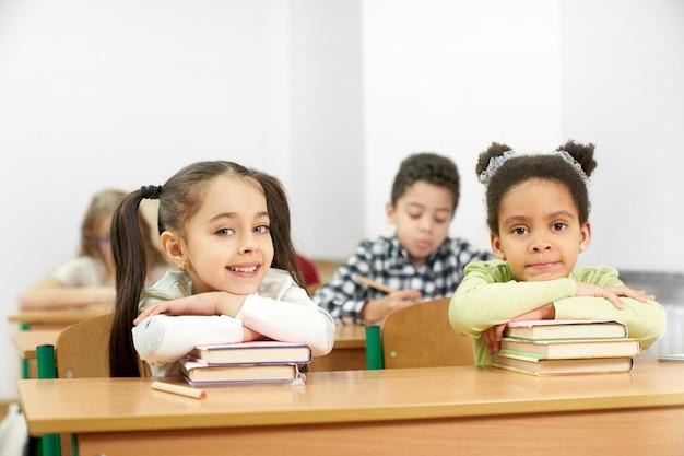 Twee charmante studenten zitten aan tafel in school en poseren Premium Foto