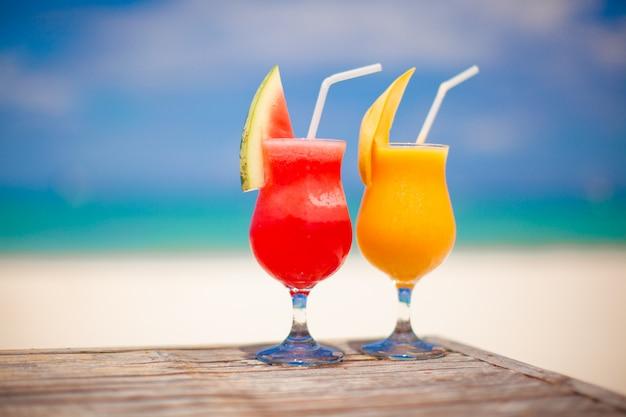 Twee cocktails: verse watermeloen en mango op de achtergrond van een prachtige turquoise zee Premium Foto