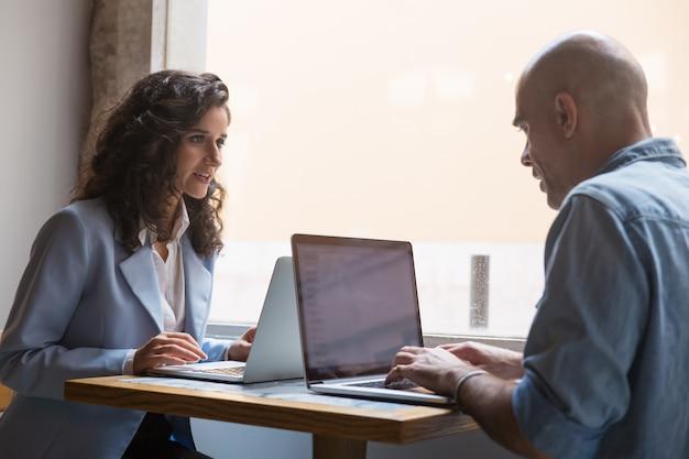 Twee collega's die laptops met behulp van tijdens onderbreking in koffie Gratis Foto