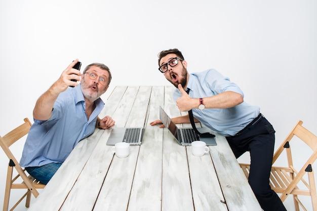 Twee collega's nemen de foto voor zichzelf op kantoor, verrast vrienden met bril selfie met telefooncamera op witte achtergrond Gratis Foto