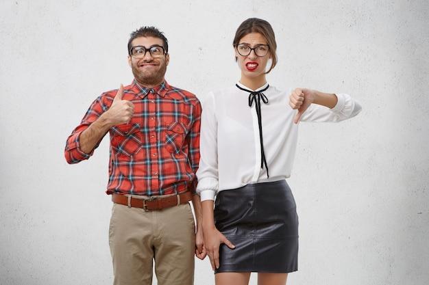 Twee collega's tonen tegengestelde emoties, vinden iets leuk en niet leuk, Gratis Foto