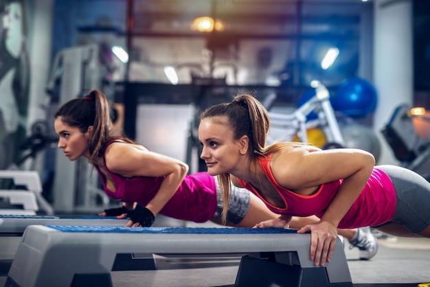 Twee dames in een sportschool doen push-ups op een stepper. sterk en toegewijd. Premium Foto