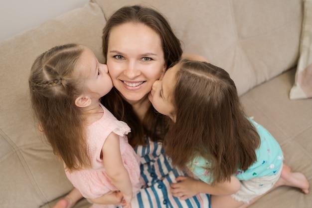 Twee dochters die hun moeder kussen Gratis Foto