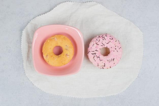 Twee donuts met sproeiers op marmeren tafel. hoge kwaliteit foto Gratis Foto