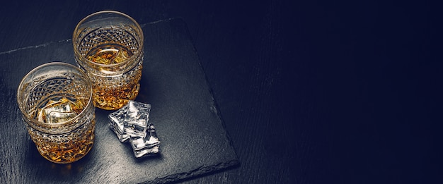 Twee dure glazen whisky met ijs op een zwart stenen dienblad Premium Foto