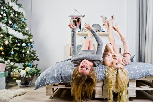 Twee elegante blonde meisjesslijtage op warme uniformjaszitting op bed tegen nieuwe jaarboom. Premium Foto
