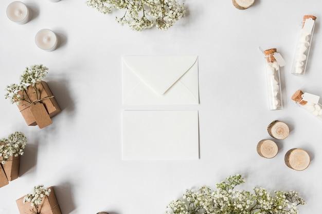 Twee envelop omringd met bloemen voor baby's; kaarsen; marshmallow reageerbuisjes; miniatuur boomstronken en geschenkdozen op witte achtergrond Gratis Foto