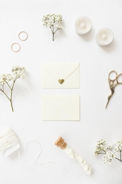 Twee enveloppen omringd met trouwringen; kaarsen; schaar; draad; reageerbuis en baby's-adem bloemen op witte achtergrond Gratis Foto